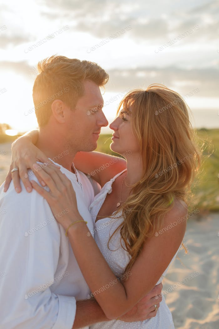 Beautiful couple embracing against sunset while dating.