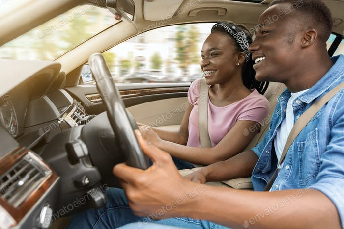 Loving black husband and wife travelling together by car