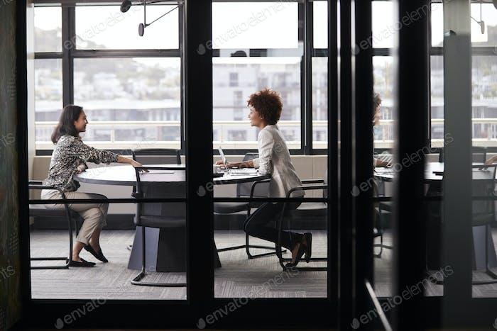 Two millennial businesswomen meeting for a job interview, full length, seen through glass wall