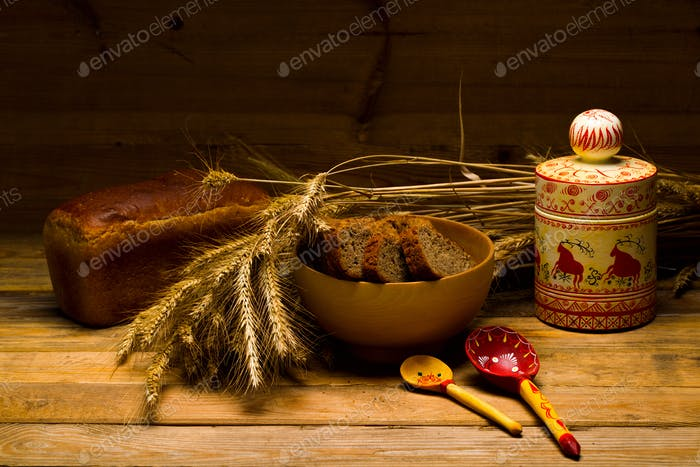 Rye bread, a loaf, ears of corn on a background of wooden boards