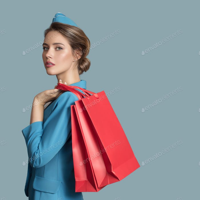 Attractive Stewardess Holding Red Shopping Bags. Duty Free.