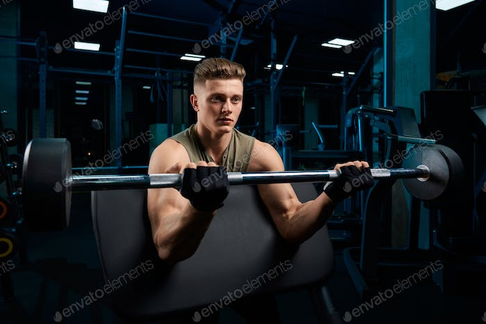 Muscular man training biceps with barbell