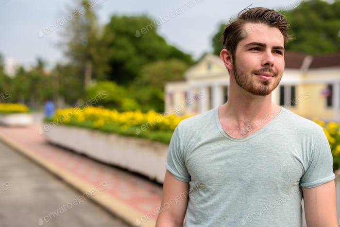 Portrait of young handsome man relaxing at the park