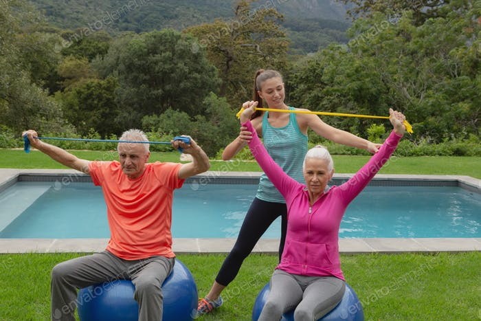 Caucasian female trainer assisting active senior Caucasian couple to exercise with resistance band