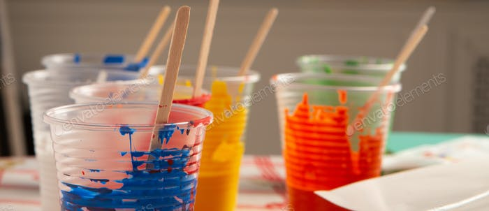 Artist acrylic colours in plastic cups in art studio