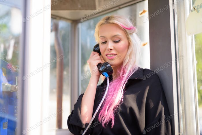 Happy young beautiful blonde woman using payphone in the streets outdoors