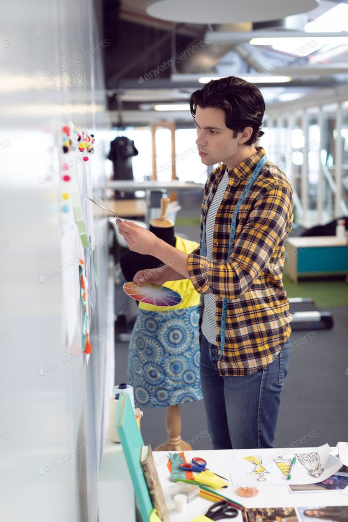 Side view of Caucasian male fashion designer looking at sketch in office
