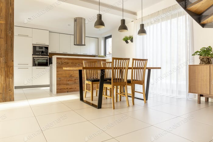 Spacious, open kitchen and dining room with wooden table and cha