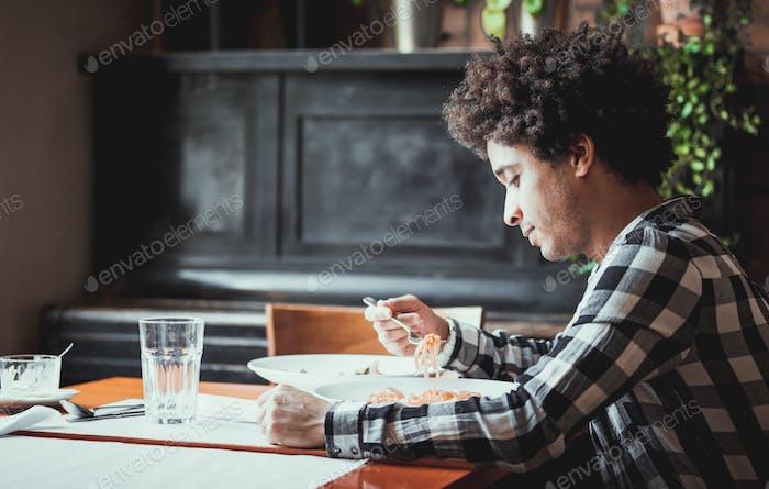 Junger afrikanisch-amerikanischer Mann isst im Restaurant zu Mittag