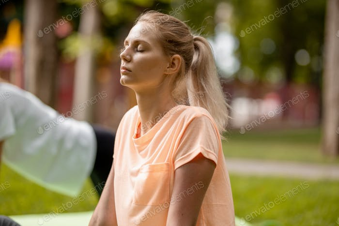 Young slender girl with closing eyes doing yoga exercises on the yoga mat on green grass in the park