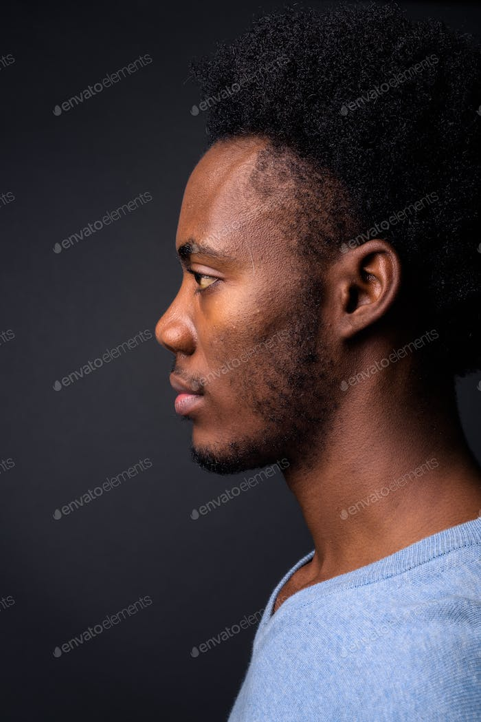 Face of young handsome African man against gray background