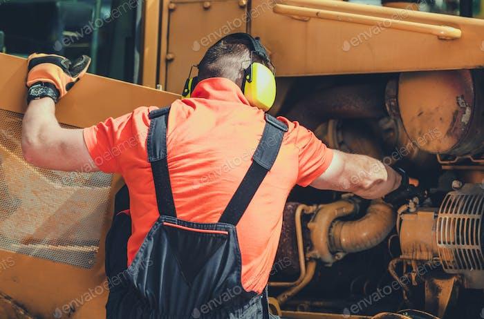 Repairman Inspecting And Adjusting Engine In Bulldozer.