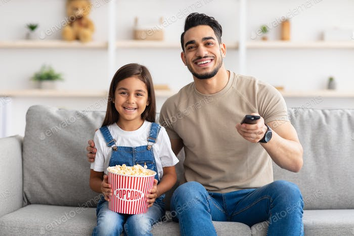 Happy young family watching television lying on floor