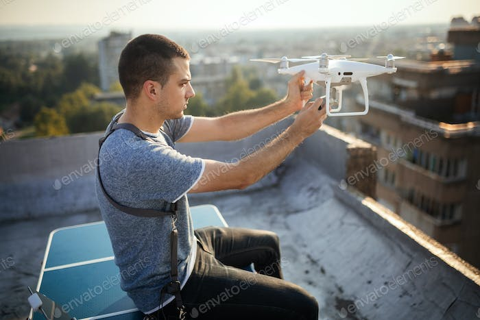 Man operating a drone with remote control on rooftop