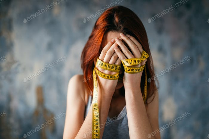 Woman covers face, hands tied with measuring tape