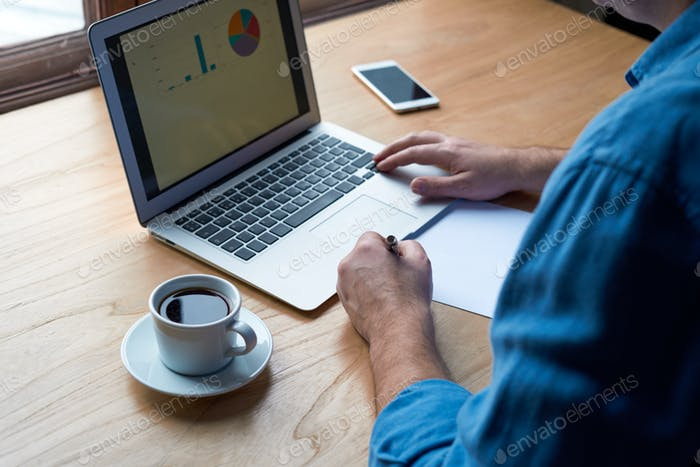 Unrecognizable man writes plan on paper and looks at charts on computer