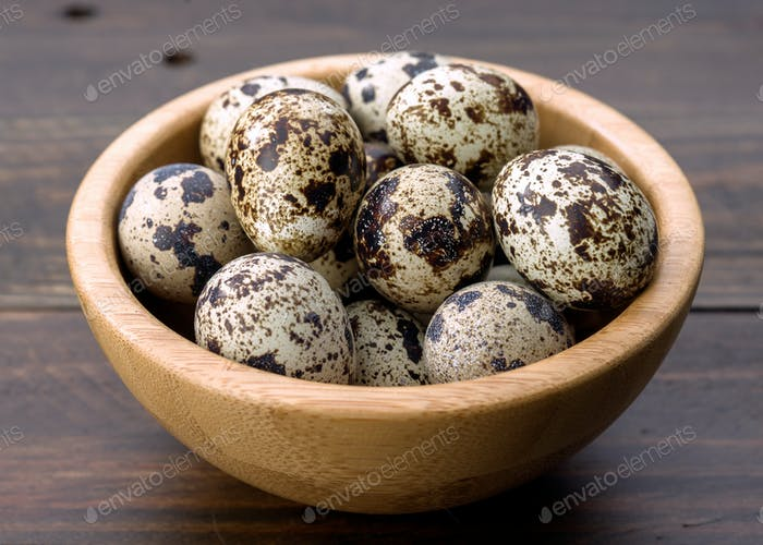 raw quail eggs on wood