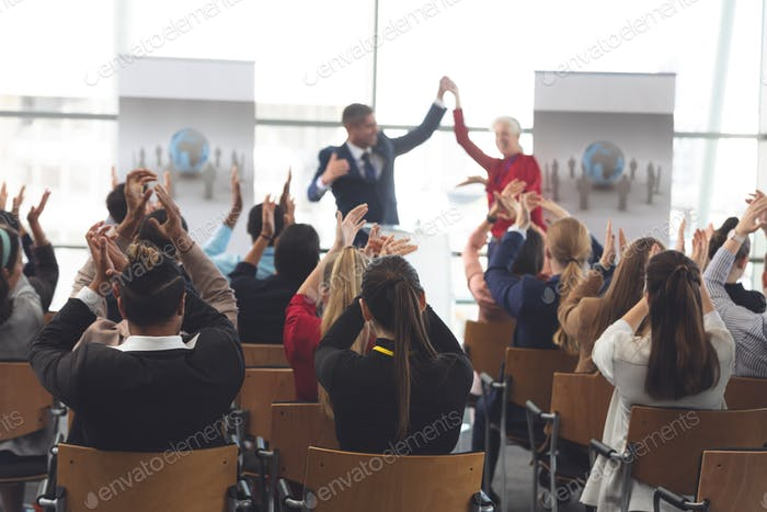 Thumbnail for Rear view of diverse business people applauding at business seminar in office building