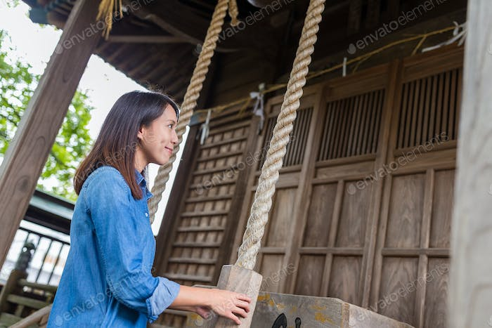 Woman ringing the bell in Japanese temple