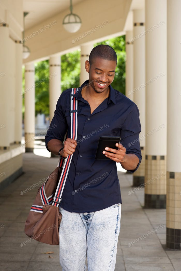 cool young black guy walking outside with mobile phone and bag
