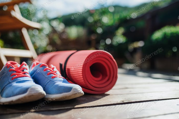 Exercise mat and trainers outdoors on a terrace in summer.