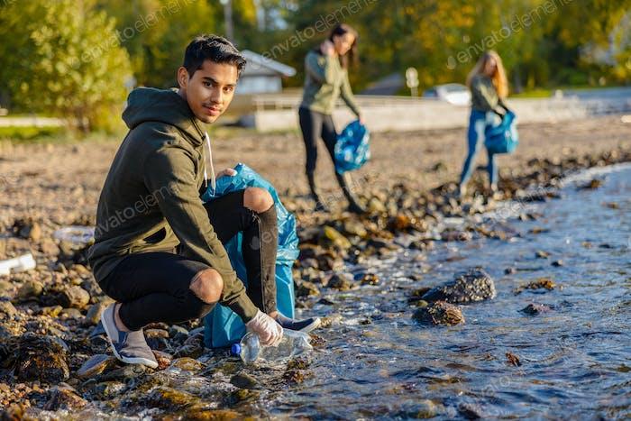 Man crouching while picking up garbage on shore