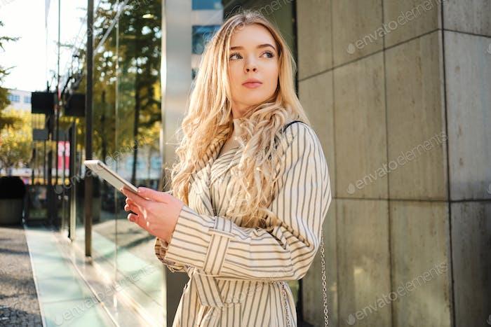 Junge attraktive Geschäftsfrau mit Tablet nachdenklich wegschauen outdoor