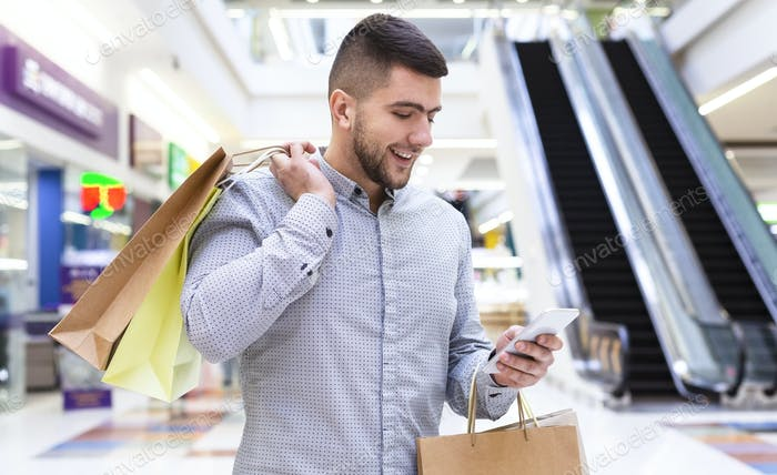 Cheerful man chatting on cellphone in shopping mall
