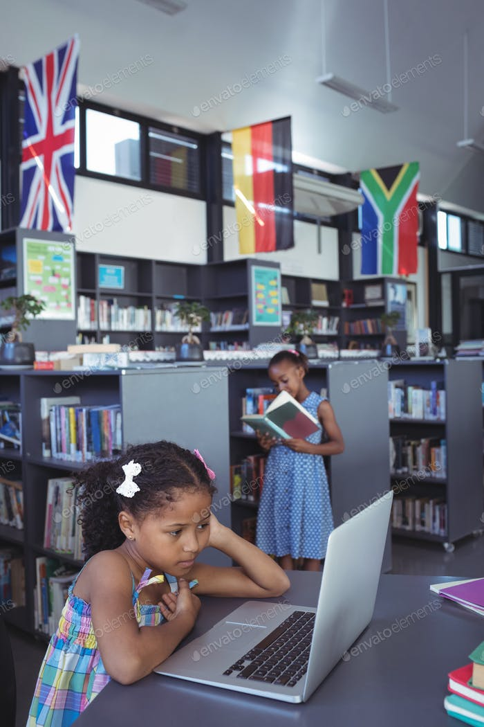 Concentrated girl looking at laptop in library