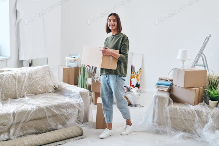 Fröhliche junge Frau in Jeans und Sweatshirt tragen verpackt Box