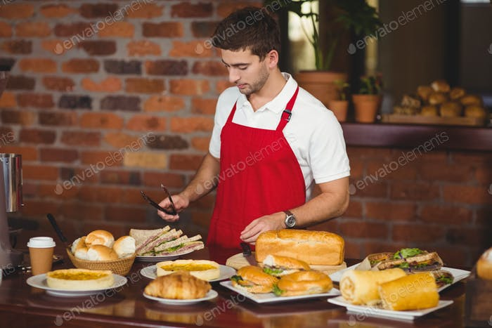 Handsome waiter about to pick a roll at the coffee shop