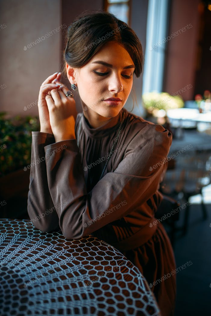Adorable dark-haired girl sitting in cafe
