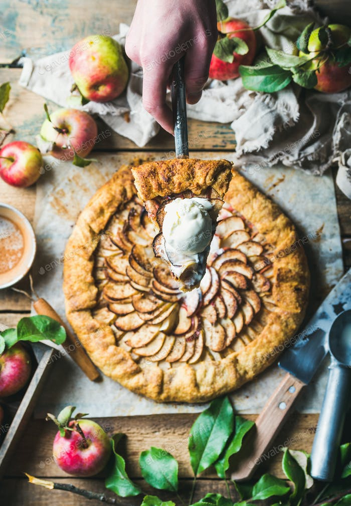 Man's hand holding piece of homemade apple crostata pie
