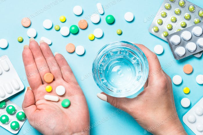 Woman takes pills on blue top view