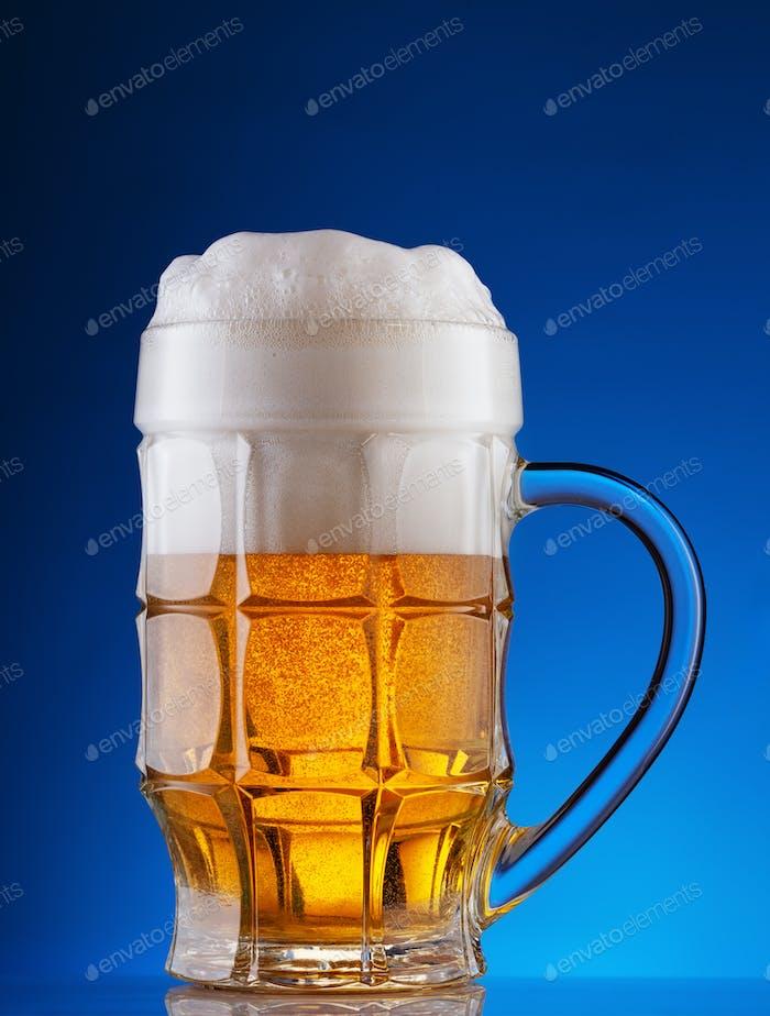 Facettierter Becher aus hellem Bier mit Schaum auf blauem Hintergrund