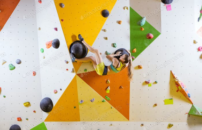 Young woman bouldering in indoor climbing gym