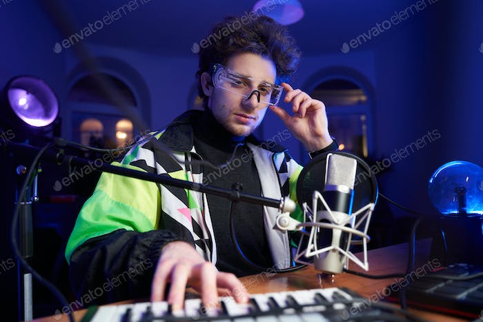Caucasian musician with glasses and musical equipment in dark room