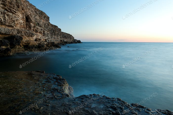 Schöner Sonnenuntergang über welligen stürmischen Schwarzen Meer felsige Küste auf der Krim am Sommertag