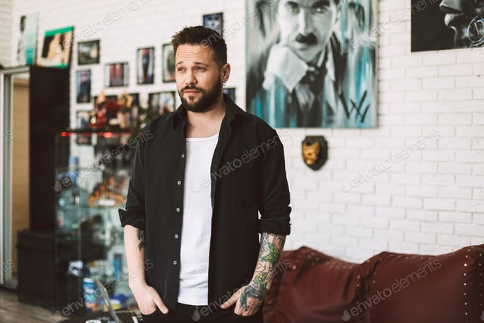 Young tattooer standing in black shirt dreamily looking aside sp