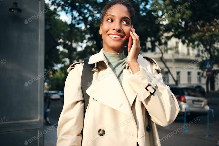 Pretty smiling African American girl in stylish trench coat happily talking on cellphone outdoor