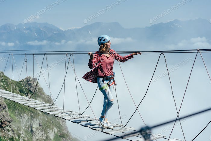 A happy cheerful woman walks on a suspension bridge high in the mountains.