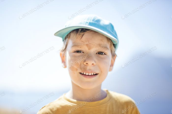 Young boy with with dirty smudges on face after playing outdoors