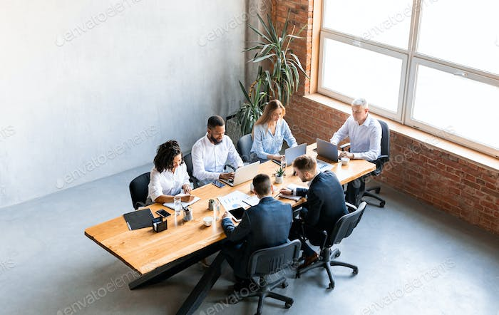 Diverse Colleagues Working Sitting Together In Modern Office, High-Angle Shot