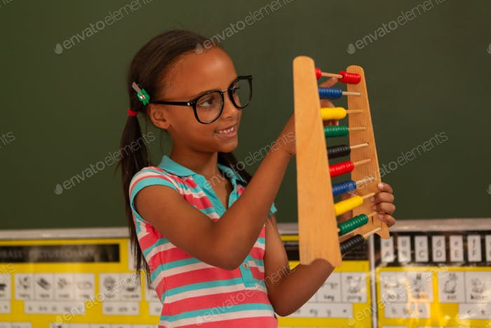 Cute schoolgirl learning mathematics with abacus in the classroom at school
