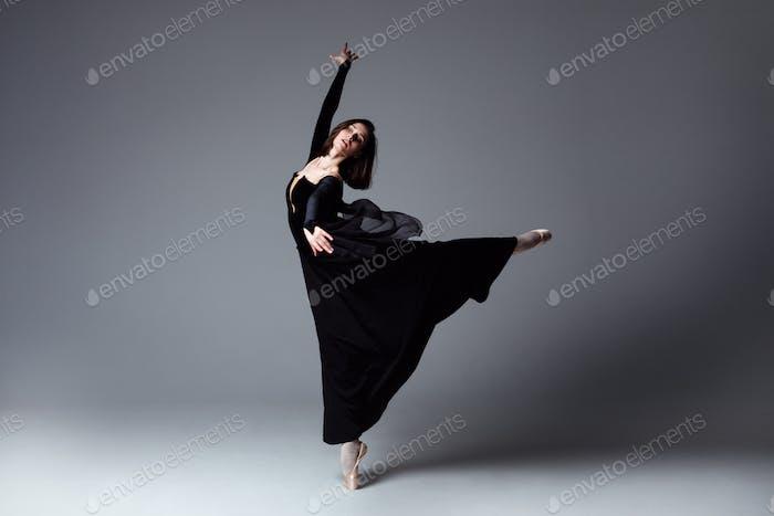 Slim ballerina in a black long dress