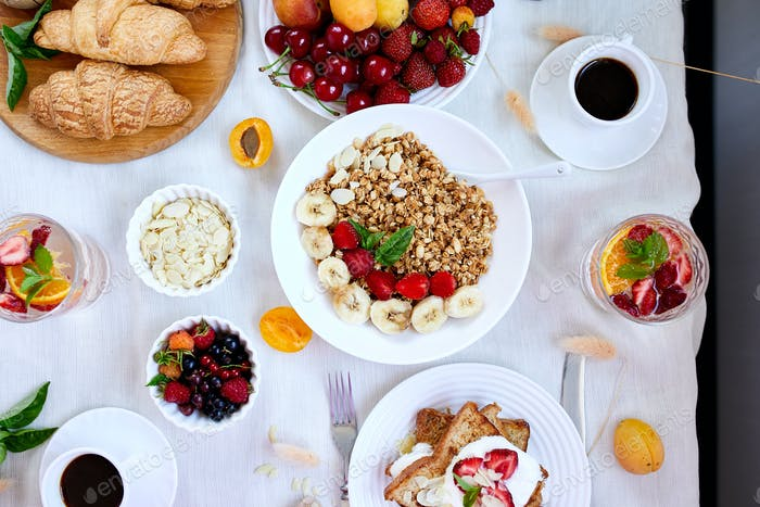 Fresh and bright continental breakfast table, abundance healthy meal variety
