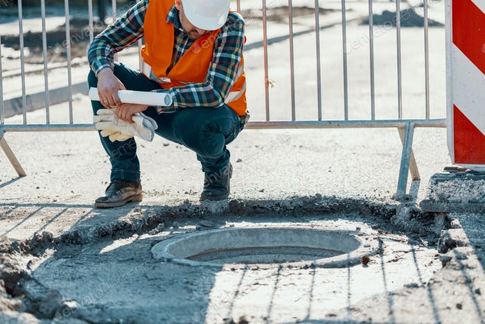 Engineer in reflective vest standing near a hole in the road dur