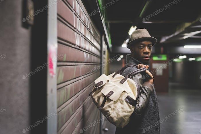 Halbe Länge der jungen gutaussehenden afro schwarzen Mann hält eine Tasche, schlank