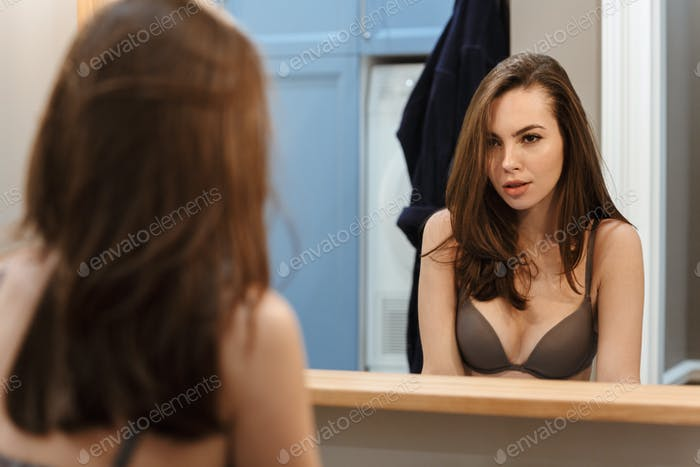 Image of seductive beautiful woman in brassiere looking at mirror