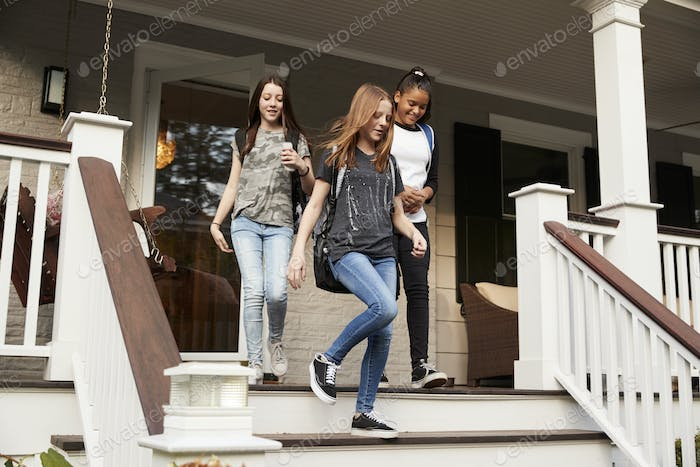 Three teen girls leaving house with school bags